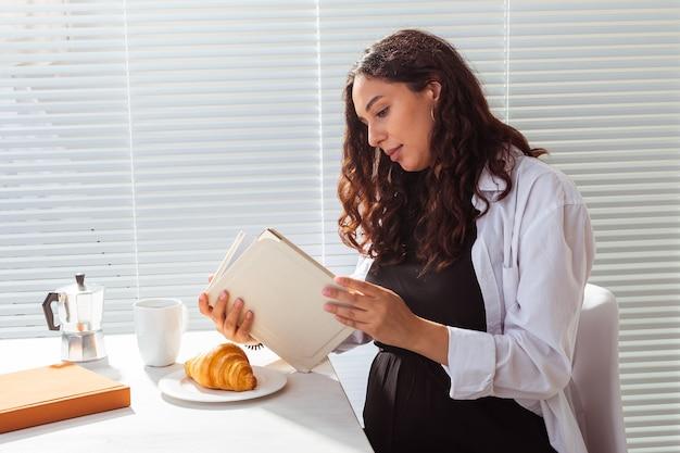 Seitenansicht der schwangeren frau, die buch liest, während morgenfrühstück hat
