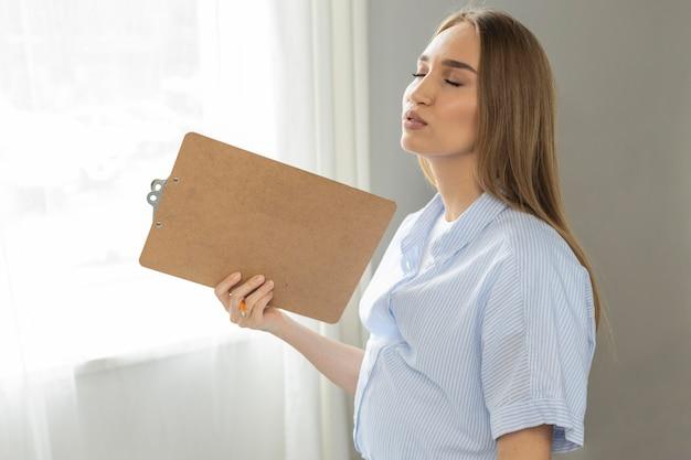 Seitenansicht der schwangeren geschäftsfrau, die zwischenablage hält, während im schmerz