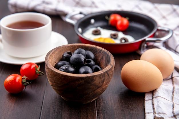 Seitenansicht der schwarzen oliven in der schüssel mit eiern tomaten tasse tee auf untertasse pfanne spiegelei auf kariertem stoff und holzoberfläche
