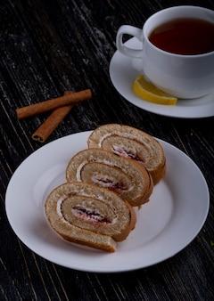 Seitenansicht der schweizer brötchenscheiben mit schlagsahne und himbeermarmelade auf einem teller, der mit einer tasse tee auf rustikal serviert wird