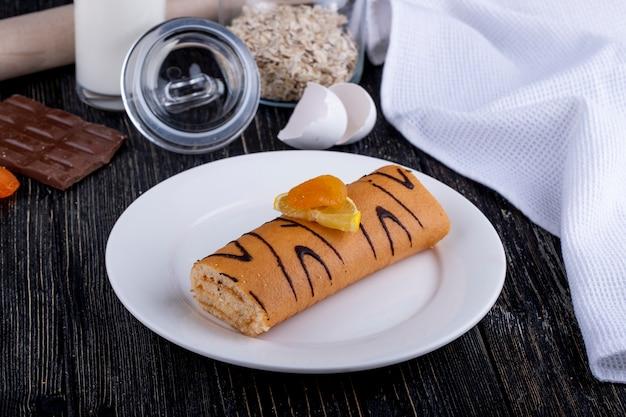 Seitenansicht der schweizer rolle mit aprikosenmarmelade auf einem weißen teller