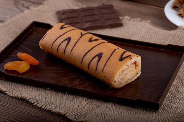 Seitenansicht der schweizer rolle mit aprikosenmarmelade auf einer schwarzen tafel