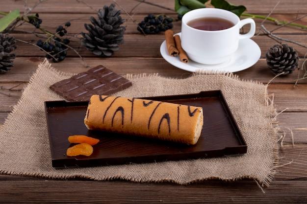 Seitenansicht der schweizer rolle mit aprikosenmarmelade serviert mit einer tasse tee auf rustikal