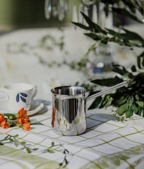 Seitenansicht der silbernen kaffeetürkenkanne auf einem küchentisch
