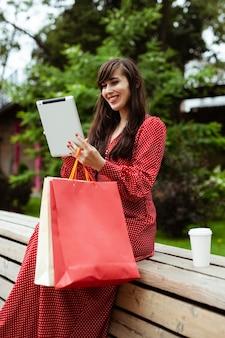 Seitenansicht der smiley-frau außerhalb der bestellung von artikeln zum verkauf mit tablette