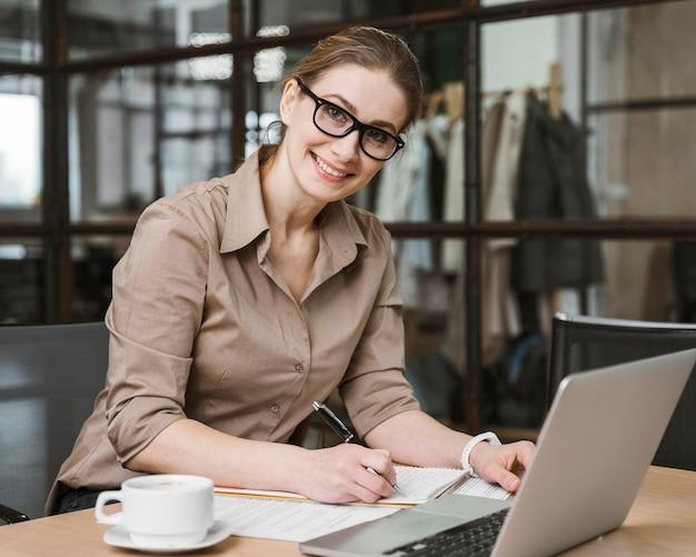 Seitenansicht der smiley-geschäftsfrau, die mit laptop am schreibtisch arbeitet