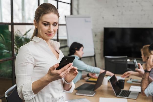 Seitenansicht der smiley-geschäftsfrau, die smartphone während eines treffens verwendet