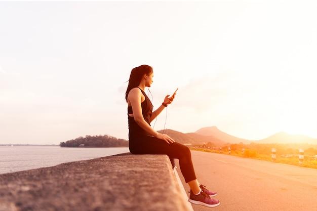 Seitenansicht der sportfrau mit den kopfhörern, die auf der wand nach dem nachmittagslauf sitzen.