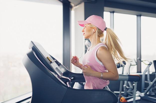Seitenansicht der sportlichen blonden frau in der rosa kappe, die auf laufband im fitnessstudio ausübt.
