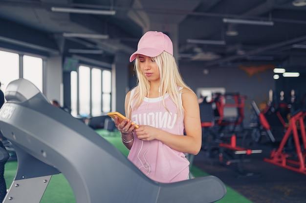 Seitenansicht der sportlichen blonden frau in der rosa kappe, die für das trainieren auf dem laufband durch auswahl der musik auf dem smartphone im fitnessstudio vorbereitet