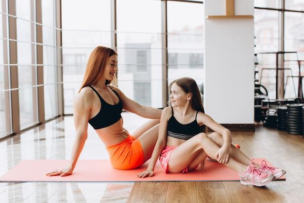 Seitenansicht der starken mutter und der tochter, die auf yogamatte im fitnessstudio sitzen