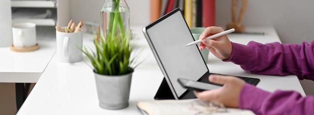 Seitenansicht der studentin, die aufgabe mit mock-up-tabelle, smartphone und briefpapier tut