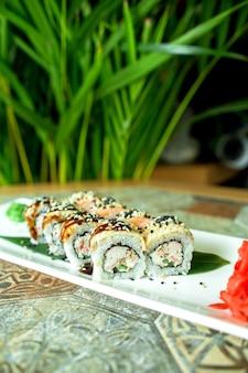 Seitenansicht der sushi-rolle der traditionellen japanischen küche mit aal-avocado und frischkäse auf grün