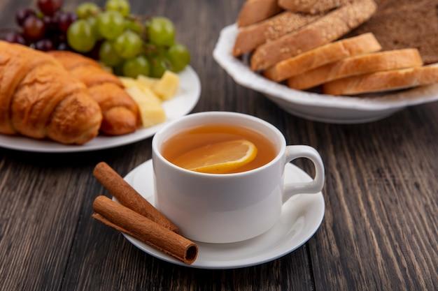 Seitenansicht der tasse des heißen wirbels mit zimt auf untertasse und croissants mit trauben und käsescheiben und broten in tellern auf hölzernem hintergrund