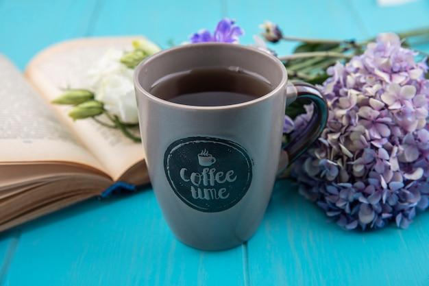 Seitenansicht der tasse kaffee mit blumen und offenem buch auf blauem hintergrund