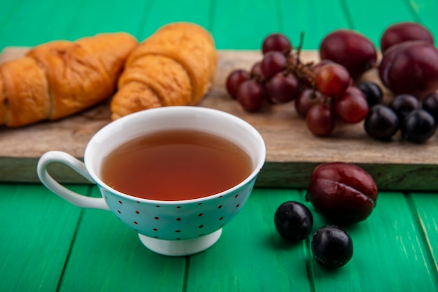 Seitenansicht der tasse tee mit croissants traubenpluots und schlehenbeeren auf schneidebrett und auf grünem hintergrund