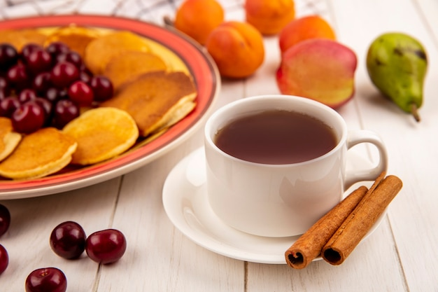 Seitenansicht der tasse tee und des zimts auf untertasse mit pfannkuchen und kirschen in teller- und birnenpfirsich-aprikosen auf hölzernem hintergrund