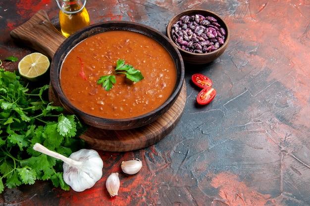 Seitenansicht der tomatensuppe auf einem braunen schneidebrett und bohnen auf einer gemischten farbtabelle