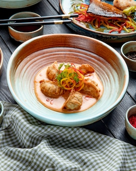 Seitenansicht der traditionellen asiatischen knödel mit fleisch und gemüse, die mit sojasauce auf einem teller auf rustikal serviert werden