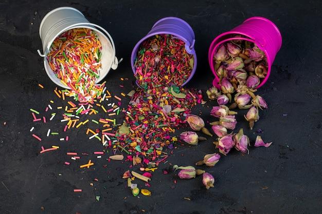 Seitenansicht der trockenen blütenblätter des rosentees und der bunten streusel, die von kleinen eimern auf schwarz verstreut werden