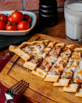 Seitenansicht der türkischen pide mit gemüsefleisch und -käse angeordnet auf einem hölzernen schneidebrett