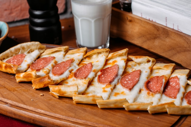 Seitenansicht der türkischen pide mit salami-wurst angeordnet auf einem hölzernen schneidebrett
