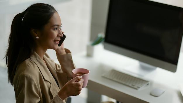 Seitenansicht der unternehmerin, die am telefon spricht, während sie eine kaffeepause im büroraum macht