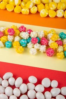 Seitenansicht der verschiedenen bunten süßen zuckersüßigkeiten auf dreifarbigem hintergrund