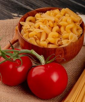Seitenansicht der verschiedenen makkaroni-arten in der schüssel mit dem holzlöffel der tomaten vom typ fadennudeln auf sackleinen und holztisch