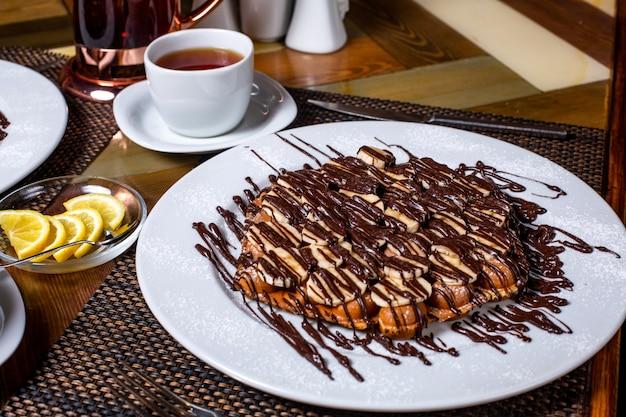 Seitenansicht der waffel mit bananen bedeckt mit schokolade auf weißem teller serviert mit tee auf dem tisch