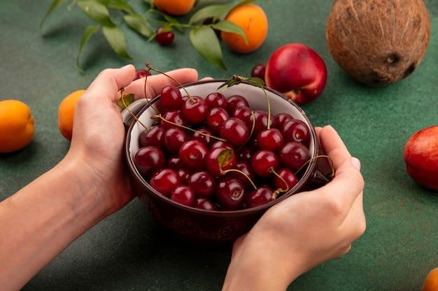 Seitenansicht der weiblichen hände, die schüssel kirschen mit muster von pfirsich-aprikosen-kirschen-kokosnuss und blättern auf grünem hintergrund halten