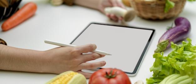 Seitenansicht der weiblichen köchin, die online bestandteile auf tablett mit leerem bildschirm bestellt