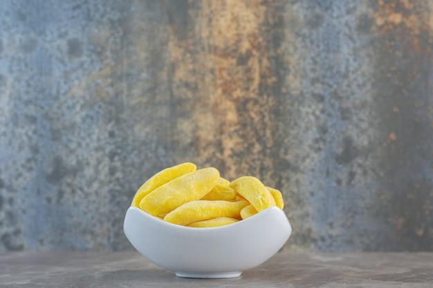 Seitenansicht der weißen keramikschale voll mit gelben bonbons.
