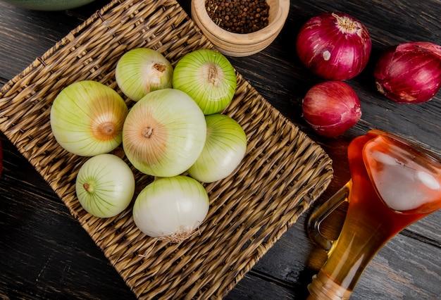 Seitenansicht der weißen zwiebeln im korbteller mit geschmolzener butter der roten und schwarzen pfeffersamen auf holzhintergrund
