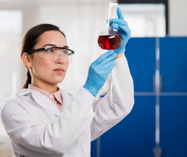 Seitenansicht der wissenschaftlerin, die laborsubstanz betrachtet
