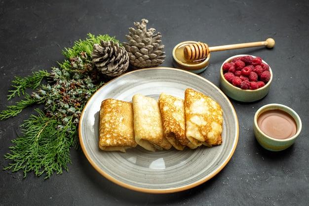 Seitenansicht des abendessenhintergrundes mit köstlichem pfannkuchenhonig und schokoladenhimbeer- und nadelbaumkegel auf schwarzem hintergrund