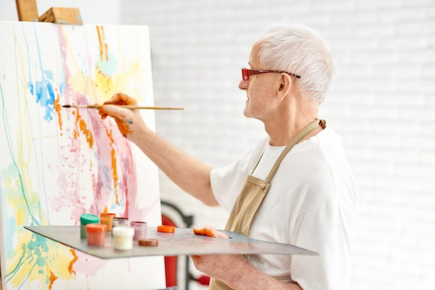 Seitenansicht des älteren begabten malers beim malen seines meisterwerks am studio der hellen kunst.