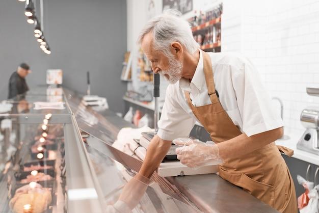 Seitenansicht des älteren männlichen metzgers, der aus der glas-gegenplatte mit geschnittenen frischen steaks herausstellt. rohe fleischstücke im kühlschrank mit preisschildern zum verkauf in der fleischabteilung. konzept des essens. Premium Fotos