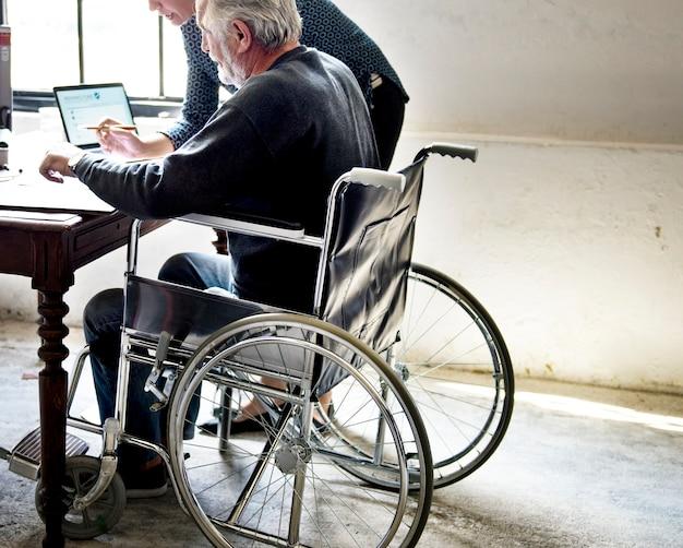 Seitenansicht des älteren mannes sitzend auf dem rollstuhl, der lebensversicherungsvertragsformular betrachtet