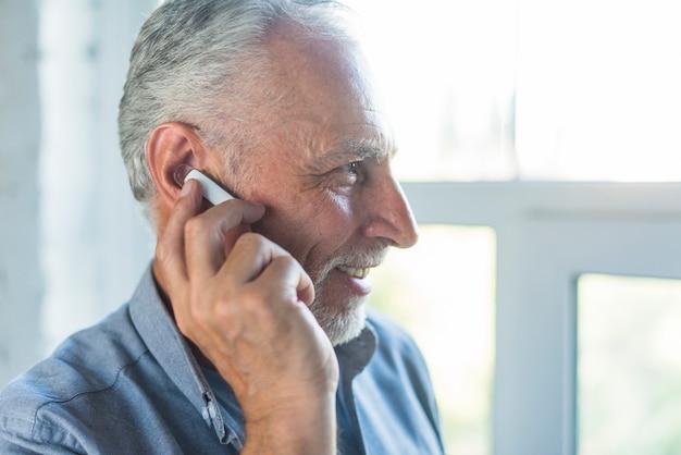 Seitenansicht des älteren mannes sprechend auf drahtlosem bluetooth kopfhörer