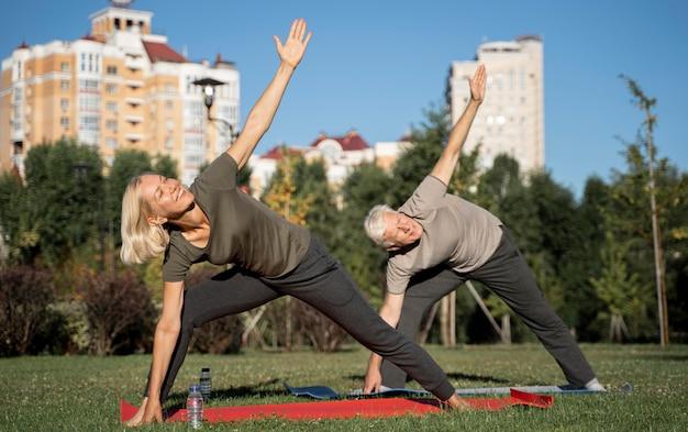 Seitenansicht des älteren paares, das yoga im freien praktiziert