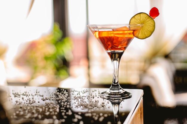 Seitenansicht des alkoholischen cocktail manhattan mit bourbonrotem vemuth bitterem eis und der cocktailkirsche im glas