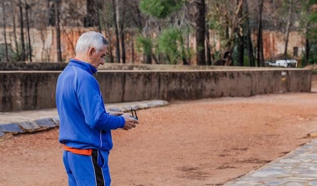 Seitenansicht des alten mannes, der die drohne in der sportbekleidung fliegt