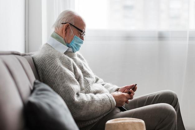 Seitenansicht des alten mannes mit der medizinischen maske in einem pflegeheim unter verwendung des smartphones