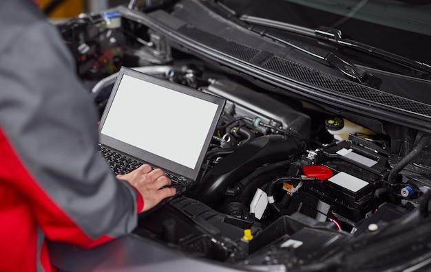 Seitenansicht des anonymen technikers der ernte, der mit laptop mit leerem weißen bildschirm arbeitet, während automotor im reparaturservicezentrum untersucht