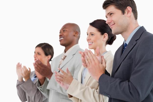 Seitenansicht des applaudierenden verkaufsteams, das zusammen steht