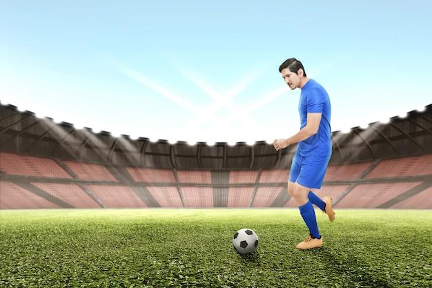 Seitenansicht des asiatischen fußballspielermannes, der den ball tritt