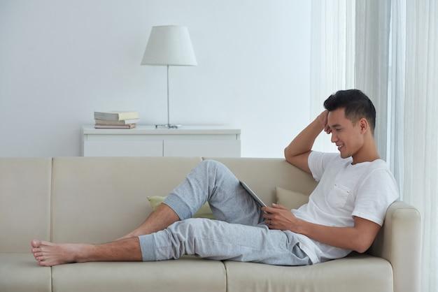 Seitenansicht des asiatischen mannes bequem gesetzt auf dem sofa und aufpassendem video auf seiner digitalen auflage