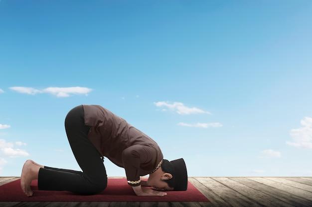 Seitenansicht des asiatischen moslemischen mannes betend