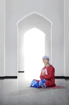 Seitenansicht des asiatischen moslemischen mannes, der den koran hält